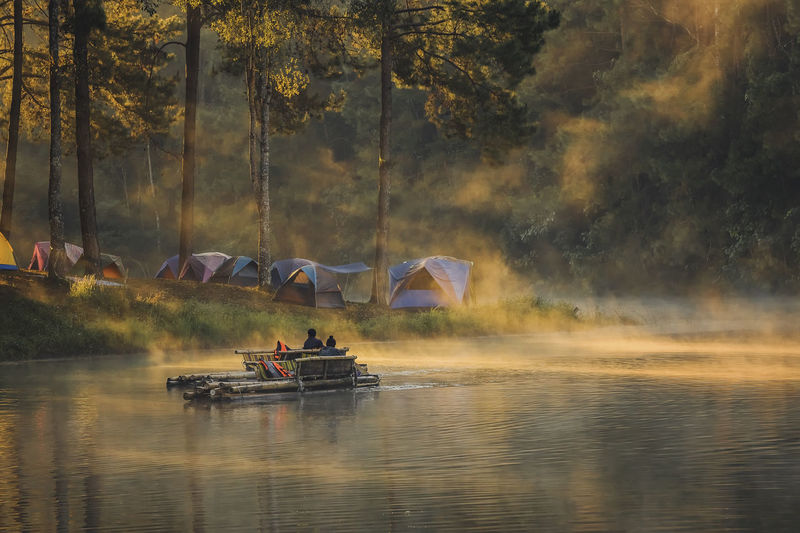 People on boat in river against trees in forest