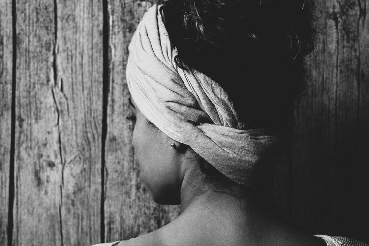 Rear view of woman wearing headdress against wooden wall