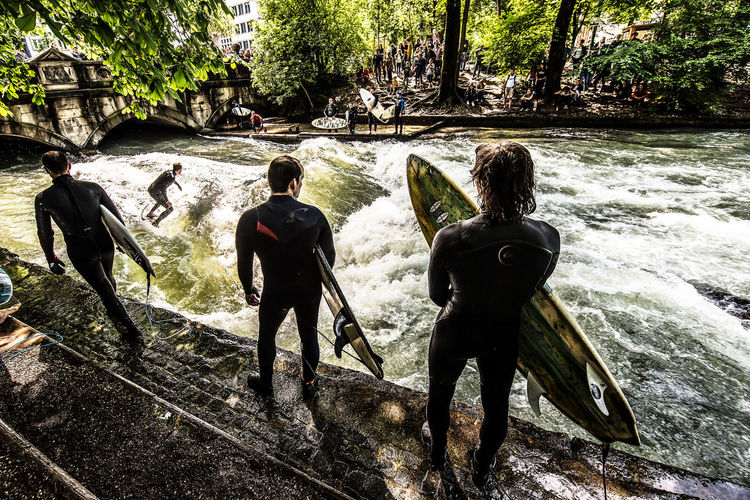 """""""Die Welle"""" Surf Beauty In Nature Day Full Length Garden Leisure Activity Lifestyles Men Nature Outdoors People Plant Real People Rear View River Standing Surfing Togetherness Tree Water"""