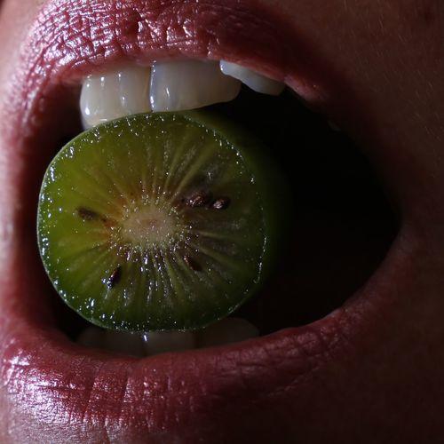 Close-up of woman eating kiwi