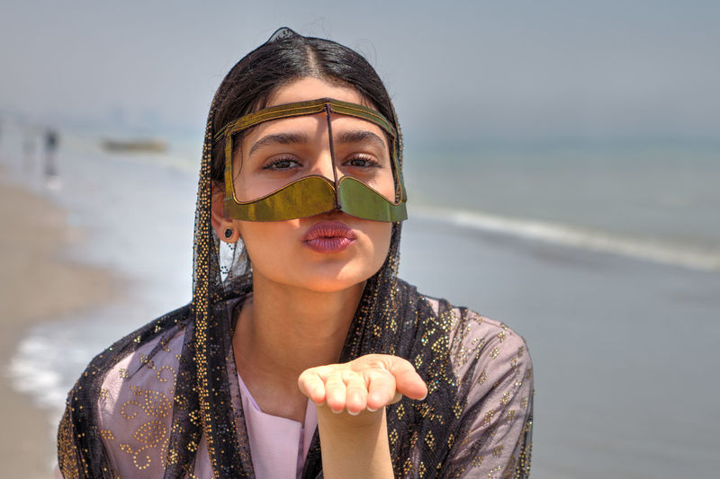 Portrait of young woman wearing traditional clothing blowing kiss at beach against sky