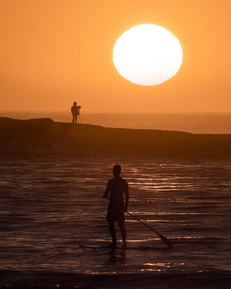Silhouette man standing on sea against sky during sunset