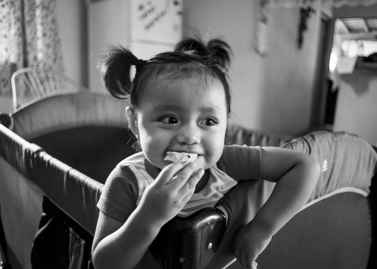 Cute Girl Eating Food While Sitting At Home