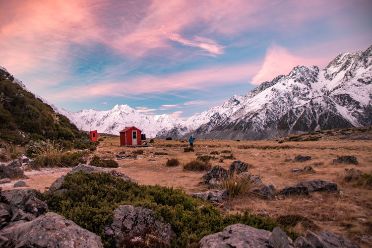 Scenic view of hut on land against snowcapped mountains and sky