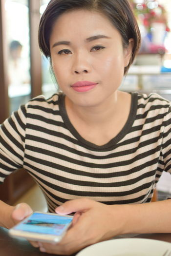 Adult Casual Clothing Focus On Foreground Front View Hairstyle Headshot Holding Indoors  Looking One Person Portrait Real People Sitting Striped Technology Waist Up Women Young Adult Young Women
