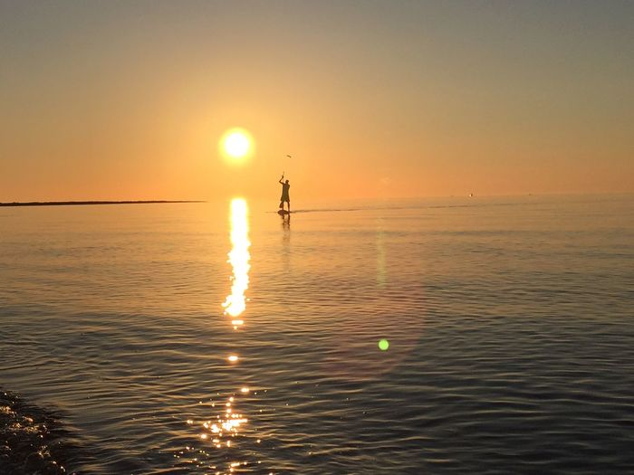 Silhouette Man Paddleboarding In Sea Against Clear Orange Sky