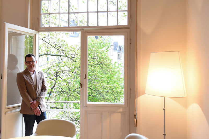 Portrait of smiling businessman standing near balcony by illuminated lamp at home