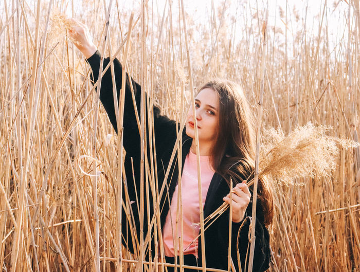 Beautiful young woman standing in field