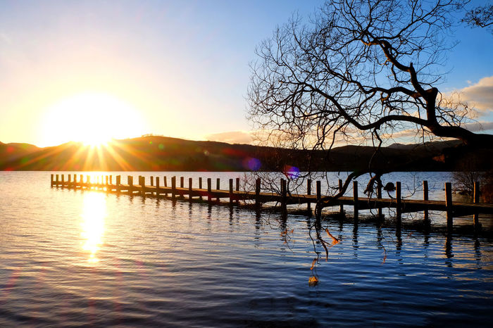 Beauty In Nature Branch Clear Sky Jetty Jetty View Lake Lake View Lens Flare Mountain Nature No People Outdoors Reflection Scenics Silhouette Sky Sun Sunbeam Sunlight Sunset Tranquil Scene Tranquility Tree Water Waterfront