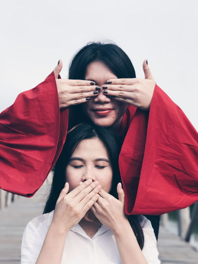 Playful female friends covering eyes and mouth with hands against clear sky