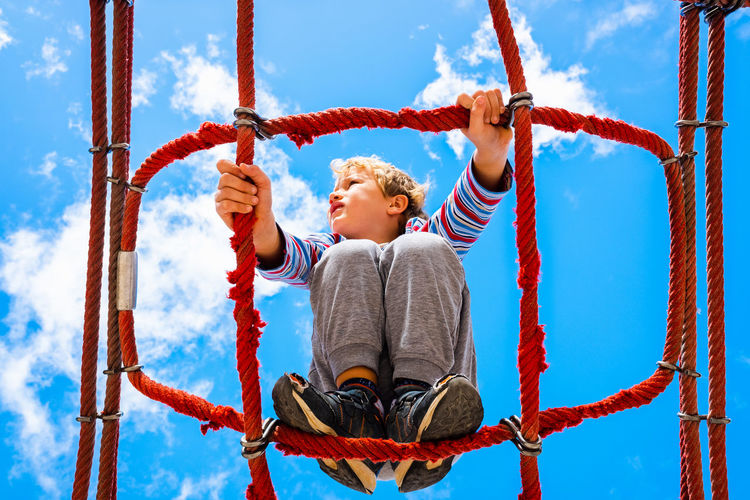 Low angle view of boy balancing on rope against sky in playground