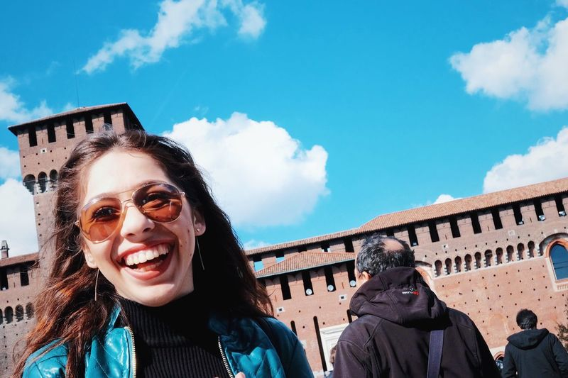 Portrait of smiling young woman against building