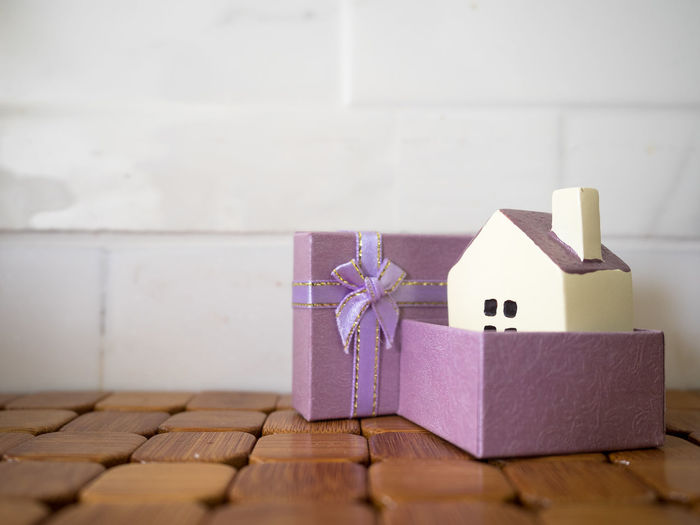 Close-up of model home in gift box on table