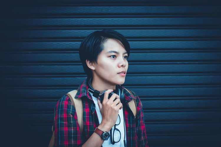 Asian man looking and hand holding headphone, vintage tone background Headphones Listening M Casual Clothing Contemplation Corrugated Hairstyle Headshot Lifestyles Looking Looking Away One Person Pattern Portrait Shutter Standing Teenage Boys Teenager Waist Up Young Adult Young Men Young Women