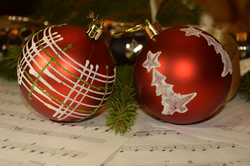 Close-up of christmas ornaments on musical notes