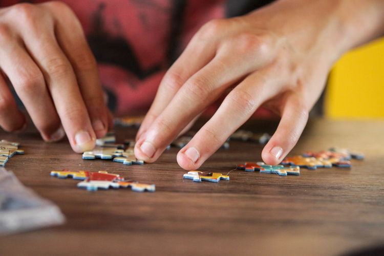 Cropped image of person playing with jigsaw puzzle on table