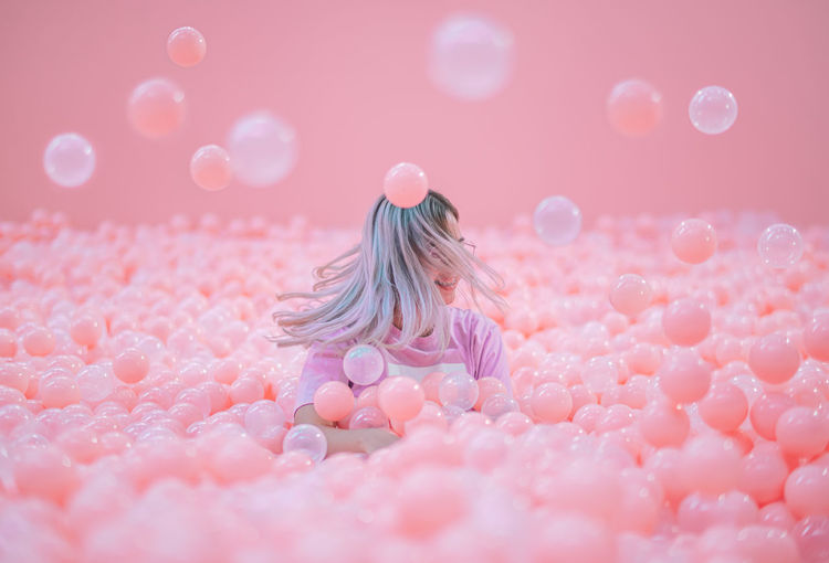 Woman shaking head while sitting in ball pool against pink background