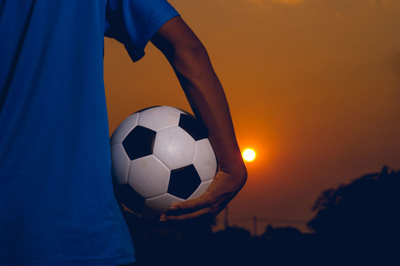 Cropped hand holding soccer ball against sky during sunset