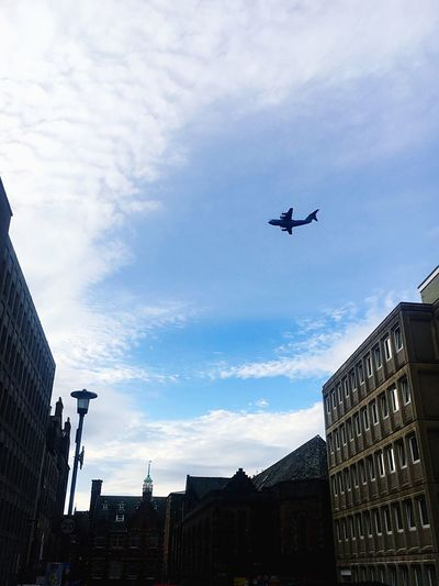 Low angle view of airplane flying over buildings in city