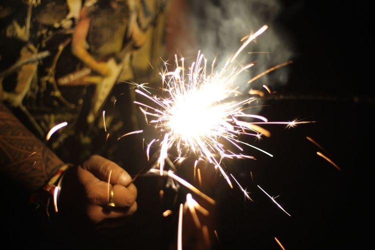 Midsection Of Man Holding Lit Sparkler