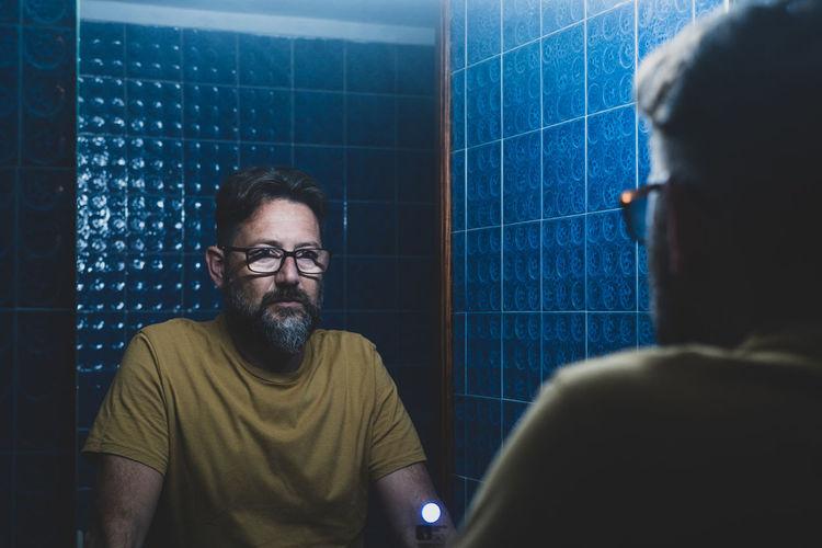 Man looking at mirror at bathroom