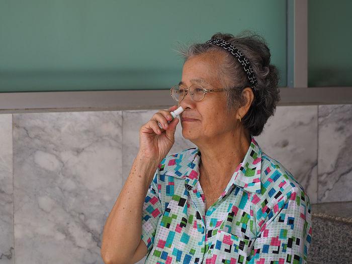 Senior woman inhaling medicine against wall
