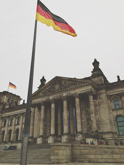 Low Angle View Of The Reichstag And German Flag Against Sky
