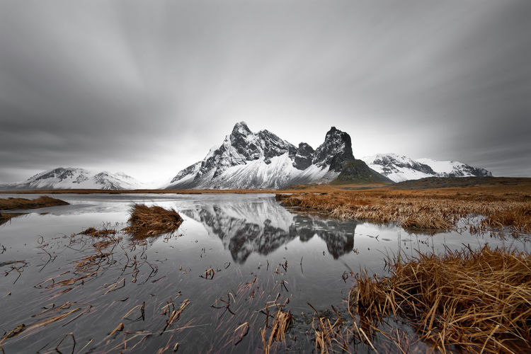 Snow-covered mountain formation is reflected in a pond, tufts of grass in and around the pond, blades of grass are partially moved by the wind, cloud movement becomes visible through long-term exposure, great depth effect - Location: Iceland, South Coast Water Environment Sky Scenics - Nature Cloud - Sky Beauty In Nature Nature No People Iceland Snowcapped Mountain Mountain Range Foreground Refelections Gray Sky Perspective Landscape Nature Season  Seasonal Travel