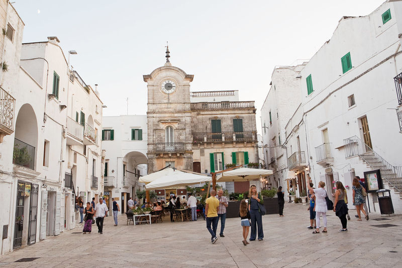 Tourists in the evening in the square in Cisternino dell'orologia August 23, 2015 Alley Alleyway Apúlia Borgo Brindisi Cisternino City Clock Tower Fasano Italy Itria Large Group Of People Ostuni People Puglia Real People Salento Square Street Tower Typical Urban Village Watch