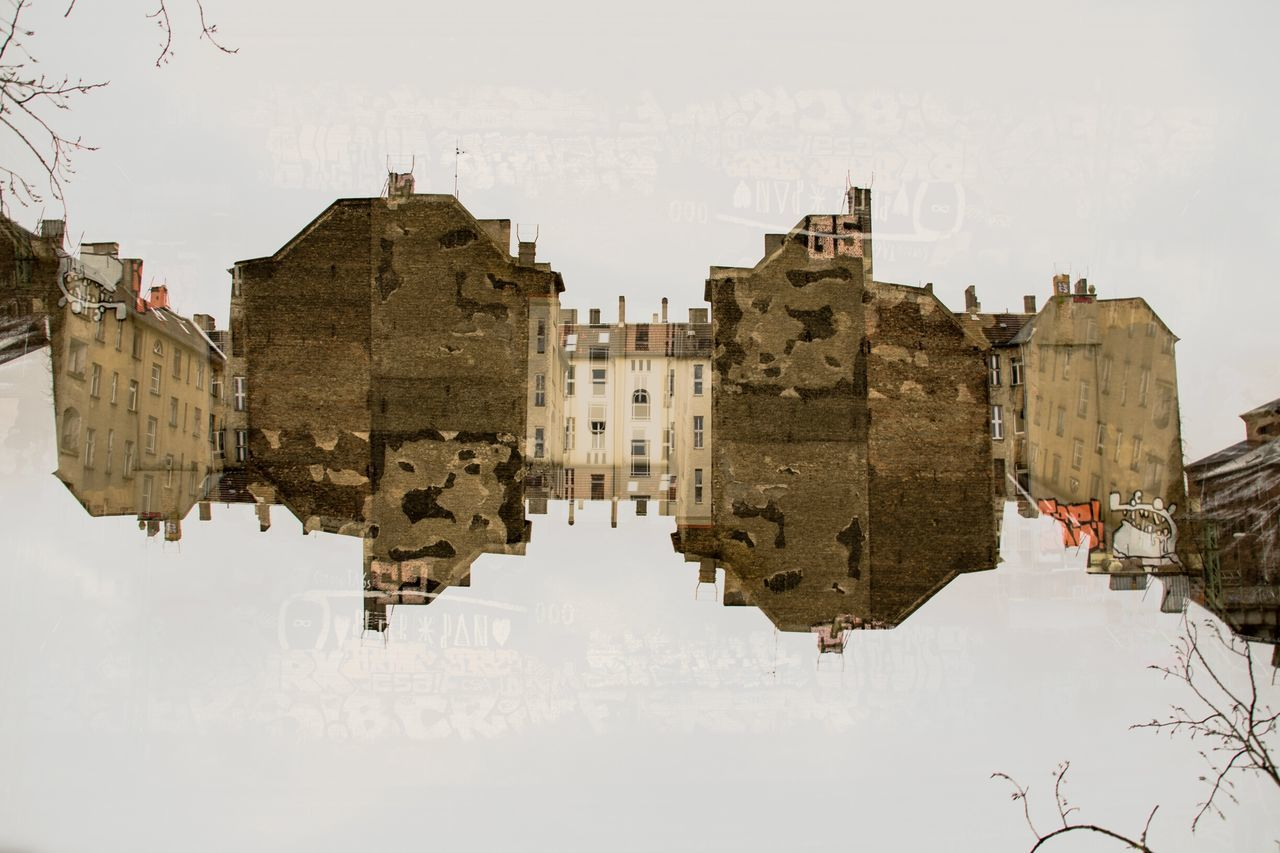 Double exposure of abandoned buildings against sky