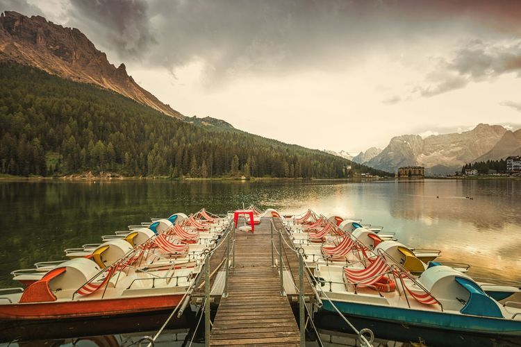 Boats Moored At Lake Misurina By Mountains Against Cloudy Sky During Sunset