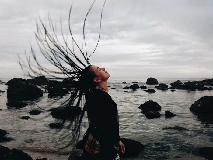 Side View Of Woman Tossing Dreadlocks At Beach Against Sky