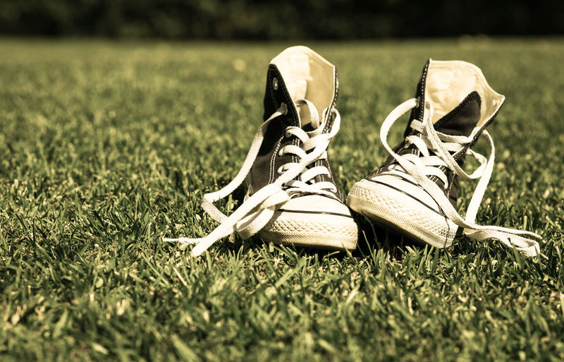 Close-up of canvas shoes on grassy field