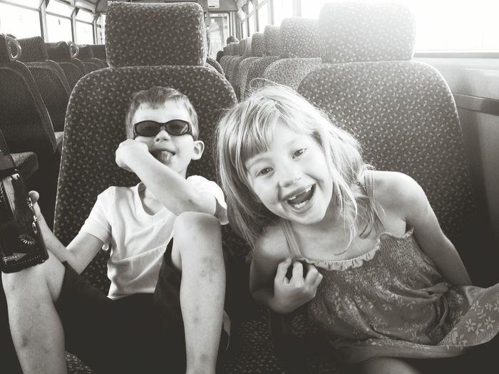 Portrait of smiling siblings in bus
