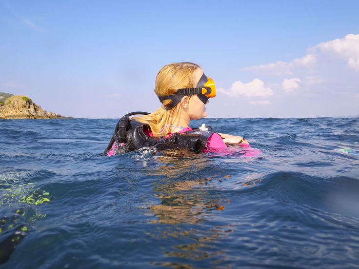Rear view of woman scuba diving in sea against sky