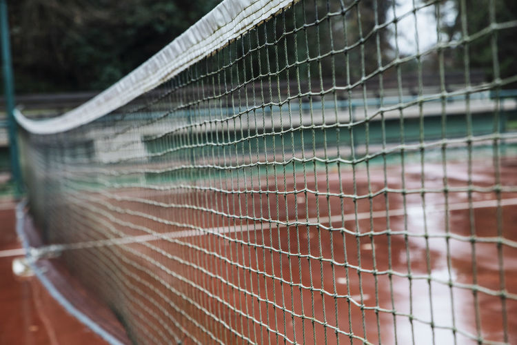 Selective Focus No People Close-up Focus On Foreground Net - Sports Equipment Day Pattern Netting Fence Outdoors Boundary Security Barrier Metal Safety Full Frame Protection Backgrounds Nature Damaged Tennis Tennis Net