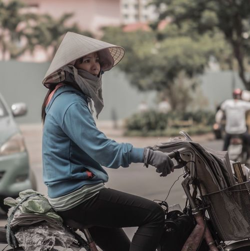 Side view of woman sitting on bicycle
