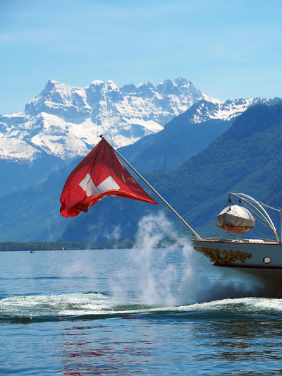 Swiss Flag On Passenger Craft Against Snowcapped Mountain