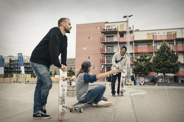 Full length of man skateboarding on city street