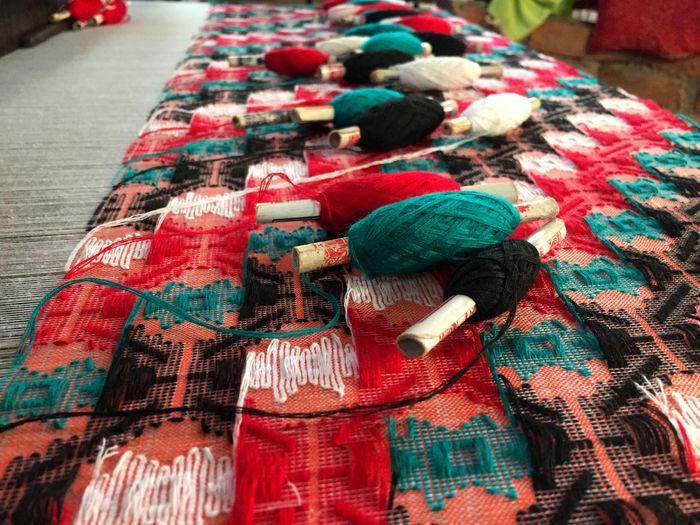 Close-up of multi colored thread spools on textile