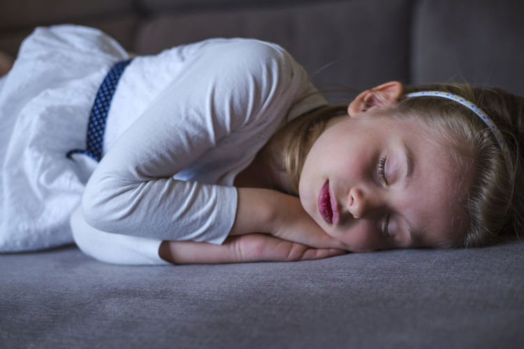 Childhood Child One Person Lying Down Indoors  Furniture Portrait Girls Women Headshot Bed Relaxation Real People Females Lifestyles Home Interior Selective Focus Innocence Contemplation