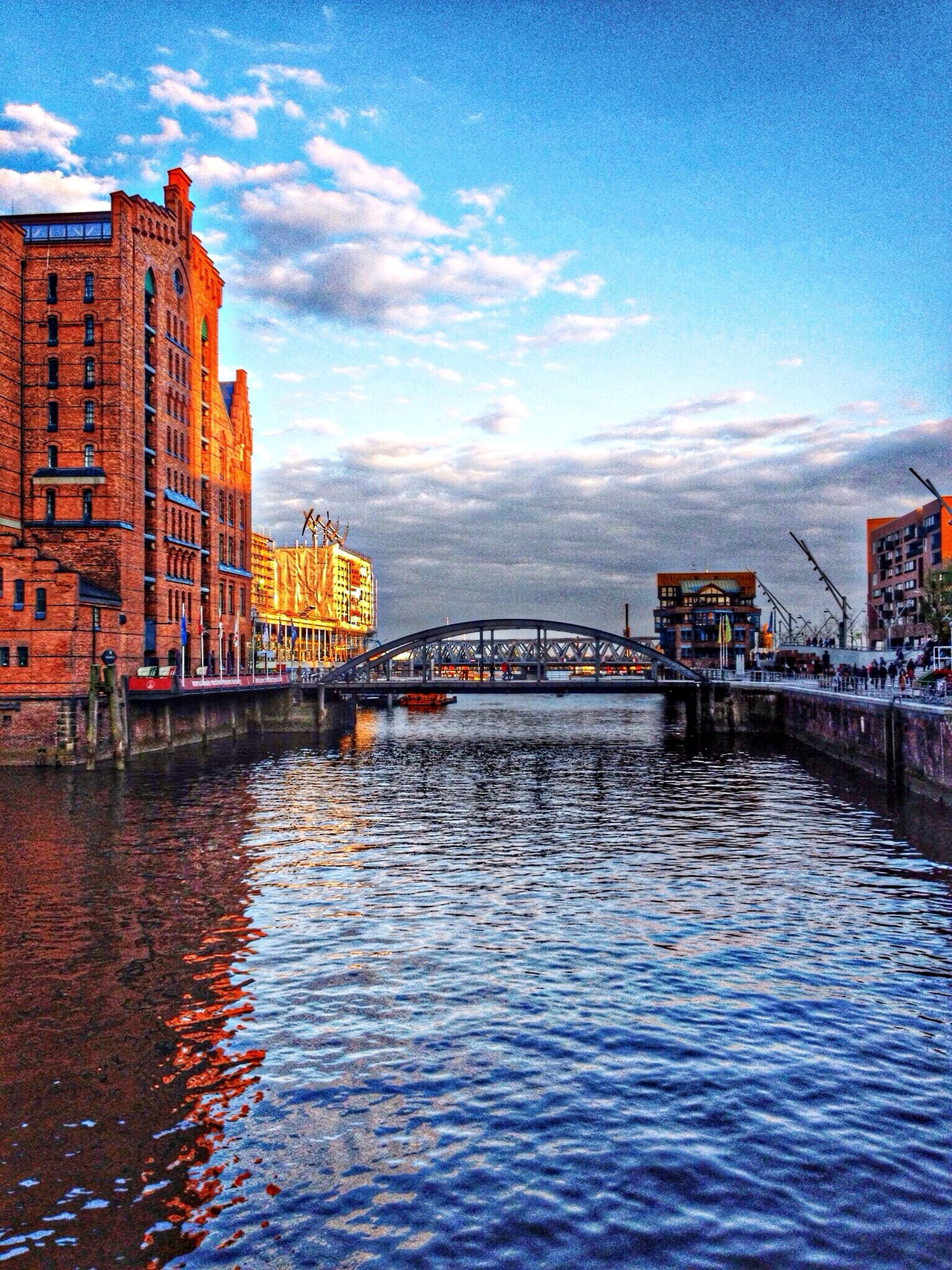 architecture, built structure, water, building exterior, waterfront, sky, bridge - man made structure, connection, river, rippled, bridge, cloud - sky, cloud, city, mountain, canal, residential structure, residential building, outdoors, no people