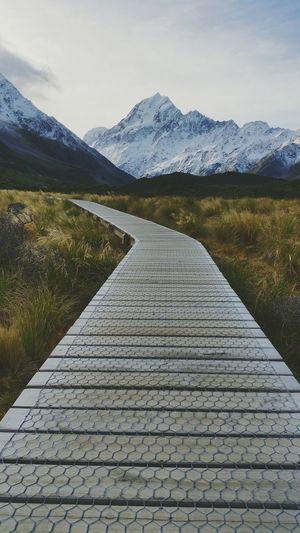 Footpath Leading Towards Mountain Range Against Sky