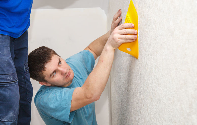 Side view of painter putting wallpaper on wall at construction site