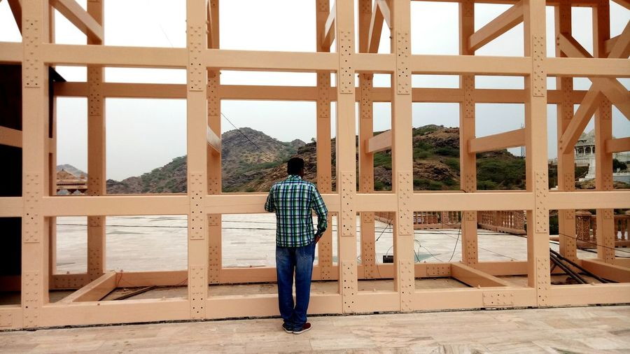 Rear view of mature man standing by built structure