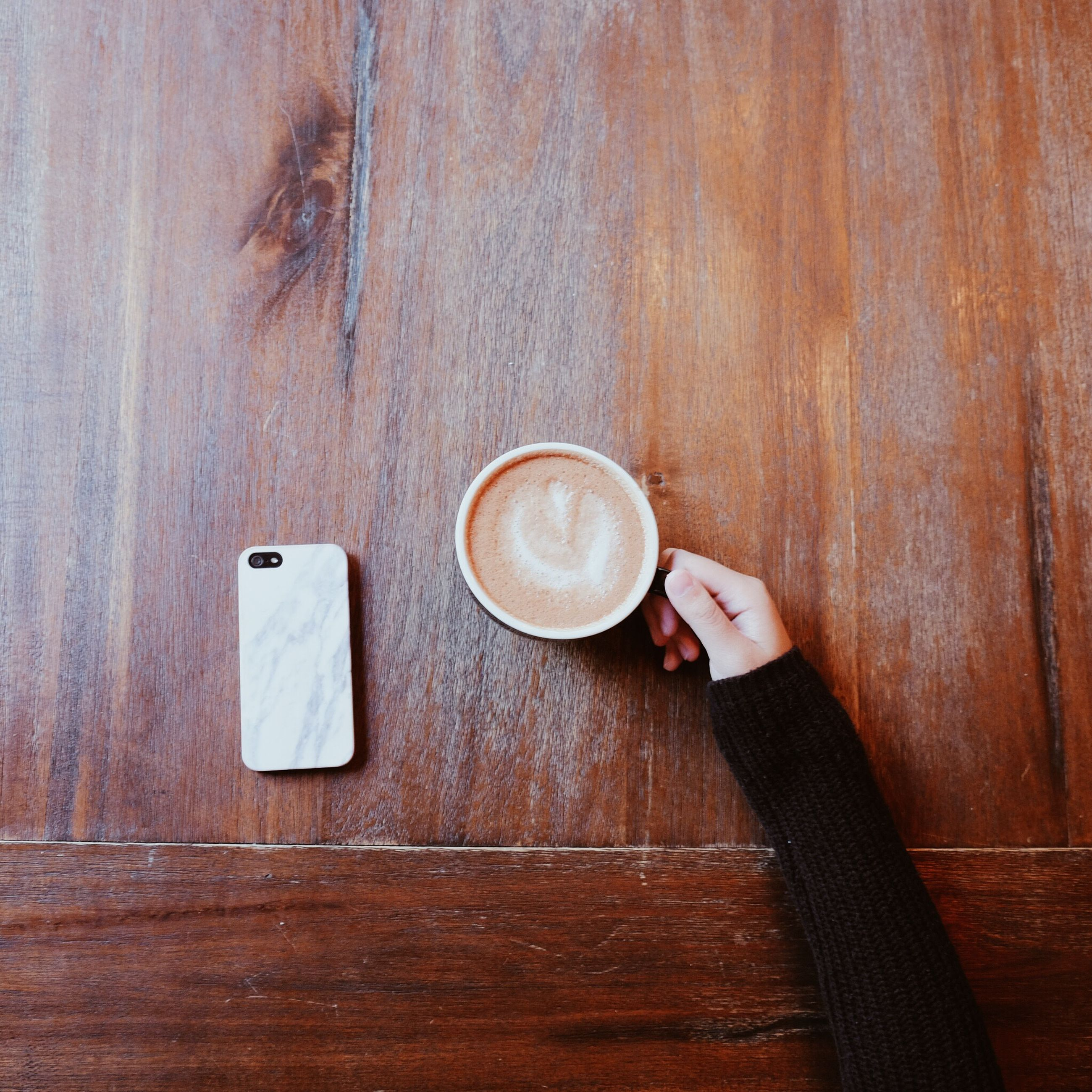 indoors, person, holding, close-up, part of, table, circle, wood - material, refreshment, drink, food and drink, coffee cup, directly above, still life, cropped, lifestyles, high angle view