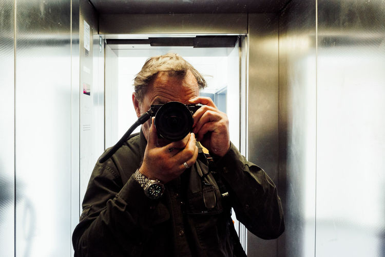 Elevator Selfie Activity Camera Camera - Photographic Equipment Digital Camera Front View Holding Indoors  Leisure Activity Lifestyles Modern Obscured Face One Person Photographer Photographic Equipment Photographing Photography Themes Portrait Real People Reflection SLR Camera Standing Technology Waist Up Camera - Photographic Equipment Camera Indoors  Adult Photographic Equipment Mirror