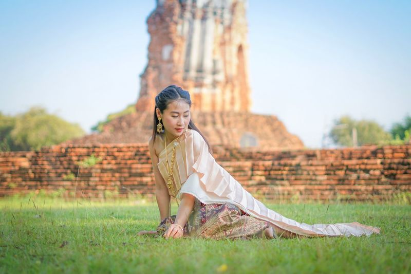 Thai traditional dress Thaigirl Thai Traditional Dress One Person Young Adult Beauty Young Women Lifestyles Clothing Full Length Fashion Outdoors Sitting Dress