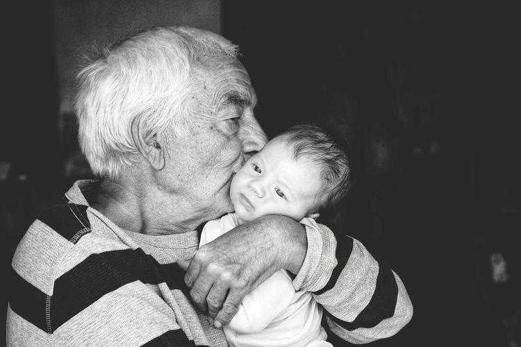Grandfather kissing grandson at night