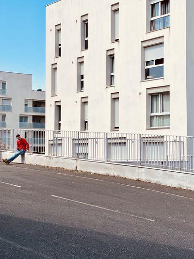 Side view of man walking on road against buildings
